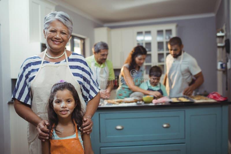 Farmor och sondotter som ler på kameran medan familjemedlemmar som förbereder efterrätten i bakgrund arkivfoto