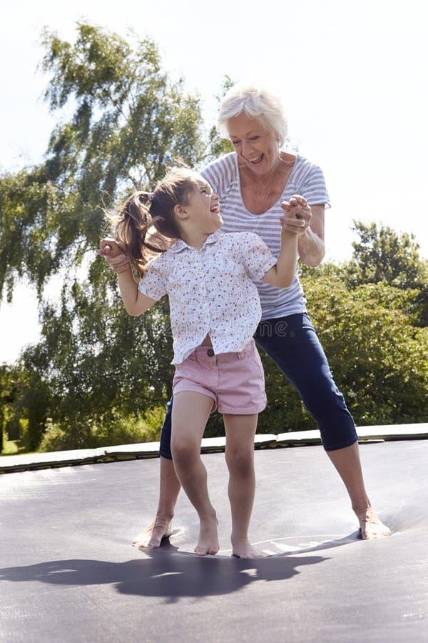 Farmor och sondotter som studsar på trampolinen royaltyfri foto