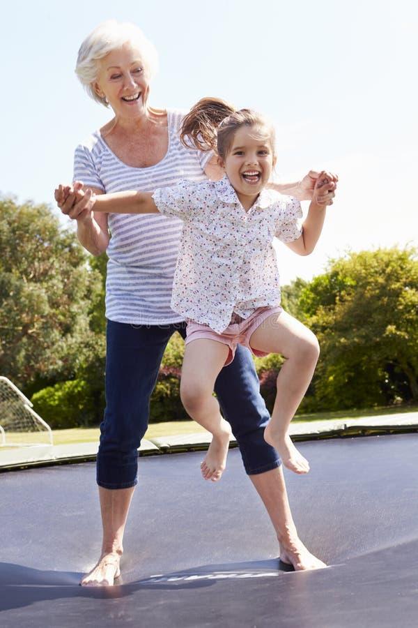 Farmor och sondotter som studsar på trampolinen arkivbild