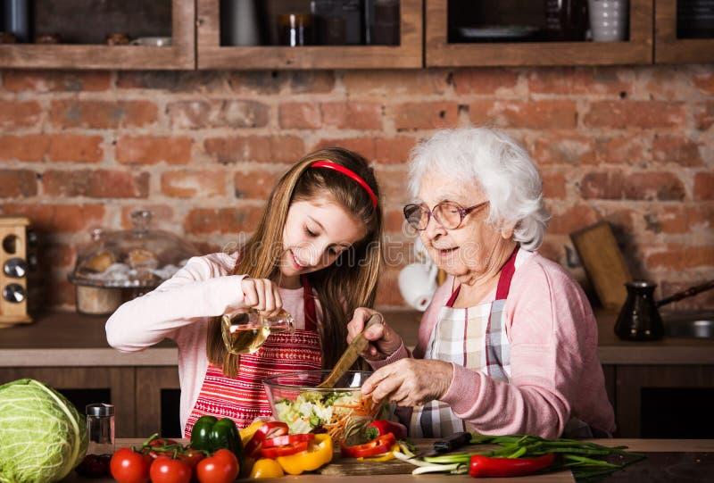 Farmor och sondotter som tillsammans lagar mat arkivbilder