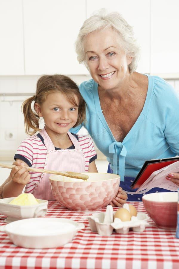 Farmor- och sondotterbakning i kök royaltyfri foto