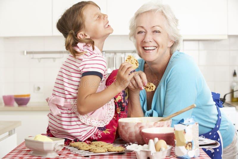 Farmor- och sondotterbakning i kök royaltyfri bild