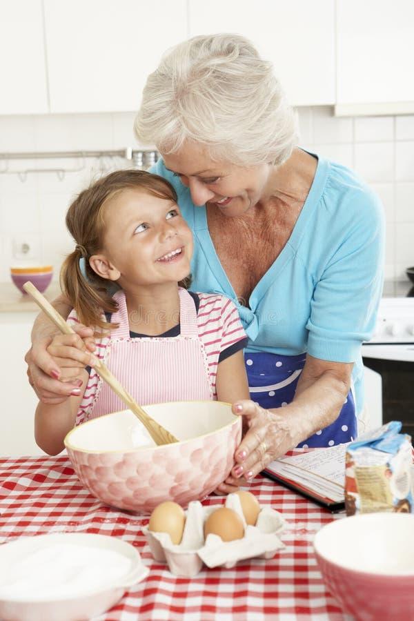 Farmor- och sondotterbakning i kök royaltyfria bilder
