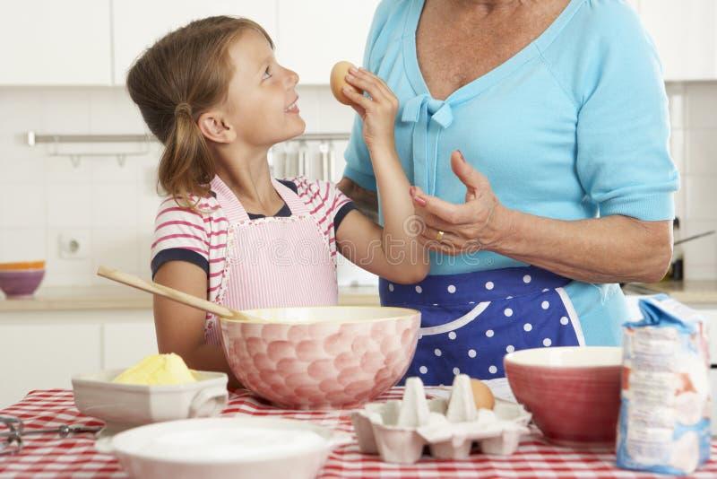 Farmor- och sondotterbakning i kök fotografering för bildbyråer