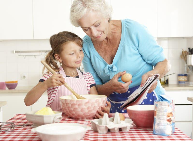 Farmor- och sondotterbakning i kök arkivfoto