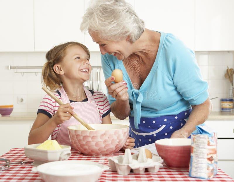 Farmor- och sondotterbakning i kök arkivbilder