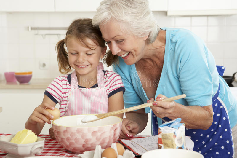 Farmor- och sondotterbakning i kök arkivbild
