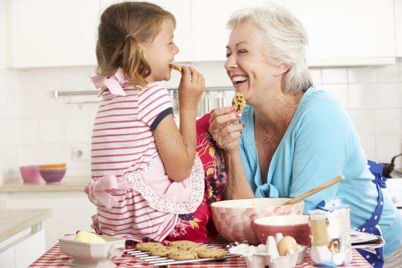 Farmor- och sondotterbakning i kök arkivfoton