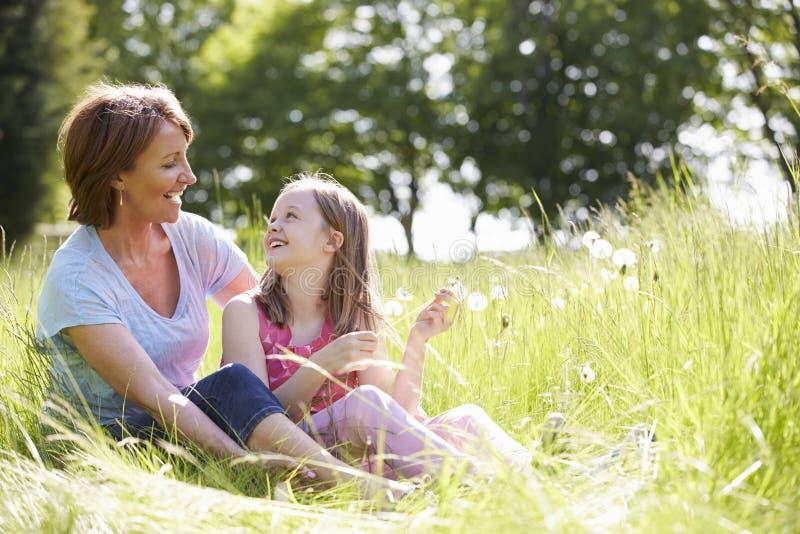 Farmor- och sondottersammanträde i sommarfält royaltyfri bild