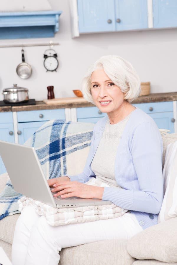 Farmor som använder bärbar datordatoren royaltyfria bilder