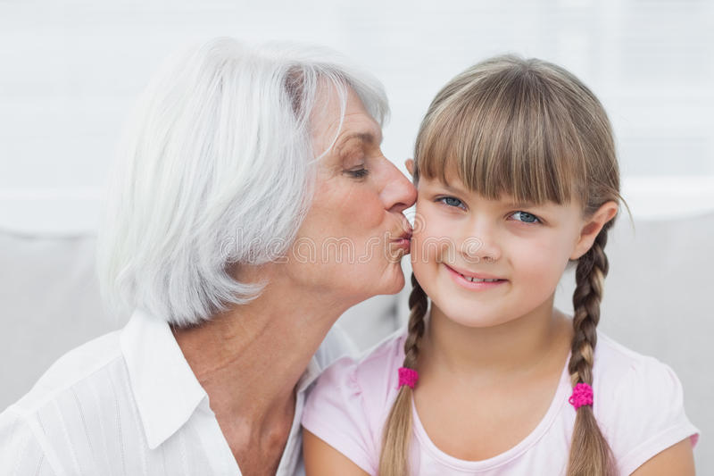 Farmor som kysser hennes gulliga sondotter arkivbild