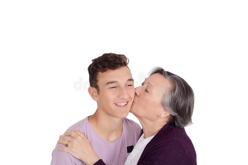 Farmor som kysser hennes tonåriga sonson royaltyfria foton