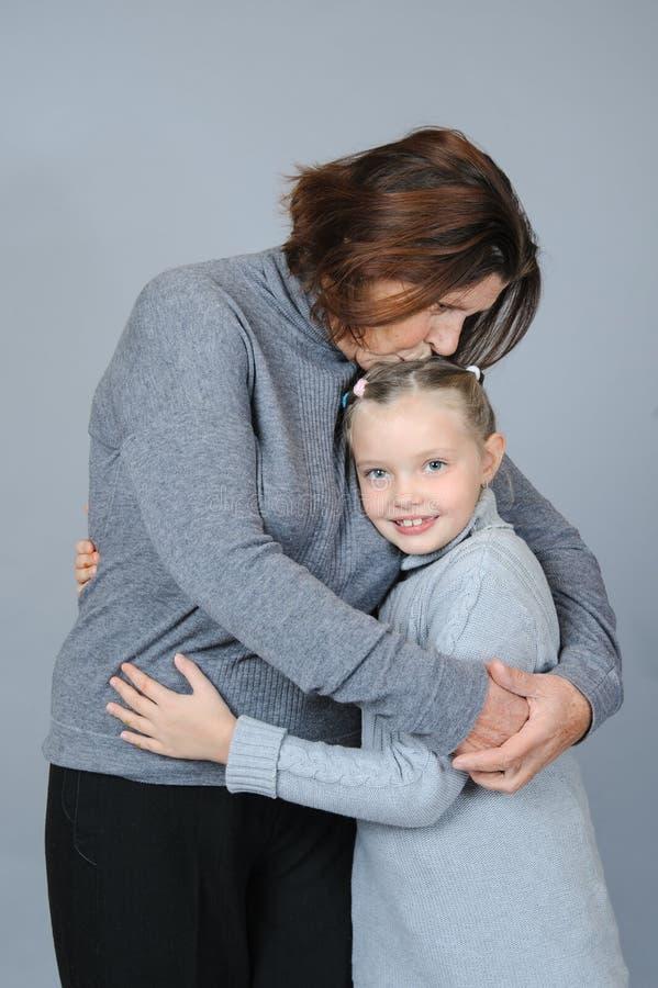 Farmor som kysser och kramar hennes sondotter royaltyfria bilder