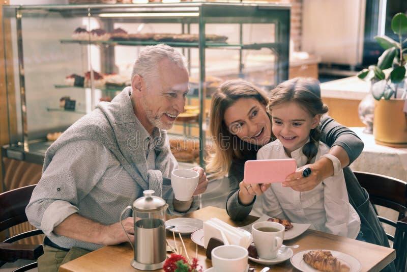 Farmor som rymmer hennes rosa smartphone som visar foto till sondottern arkivbild