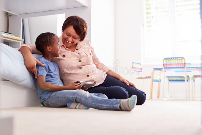 Farmor som sitter med sonsonen i det Childs sovrummet genom att använda den Digital minnestavlan tillsammans fotografering för bildbyråer