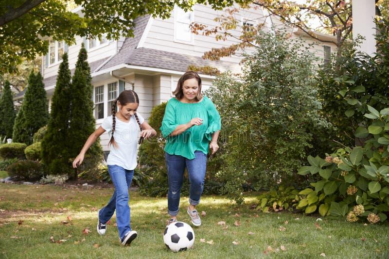 Farmor som spelar fotboll i trädgård med sondottern royaltyfria foton