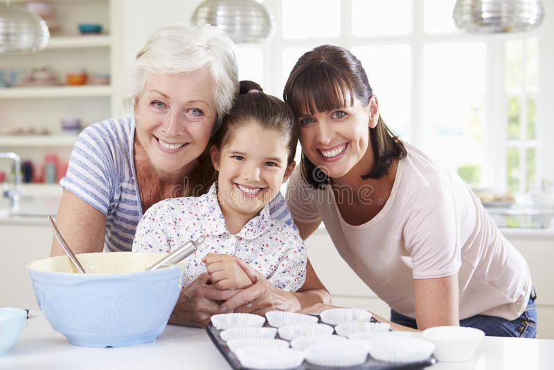 Farmor-, sondotter- och moderbakningkaka i kök royaltyfria bilder