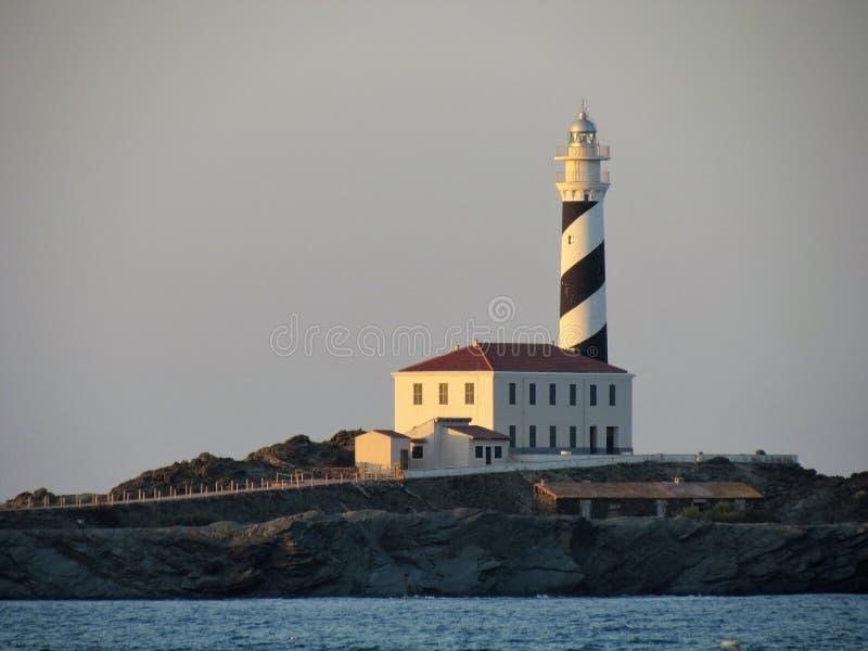 Faro al tramonto nel Baeutiful Cala Tortuga in Menorca Spagna fotografia stock libera da diritti