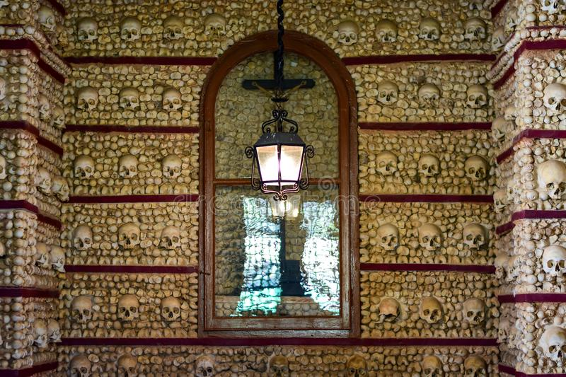 Skulls and bones are embedded in the wall. Faro, Algarve / Portugal - 07.20.2019: Skulls and bones are embedded in the wall, a lantern is lit, a crucifix behind royalty free stock images
