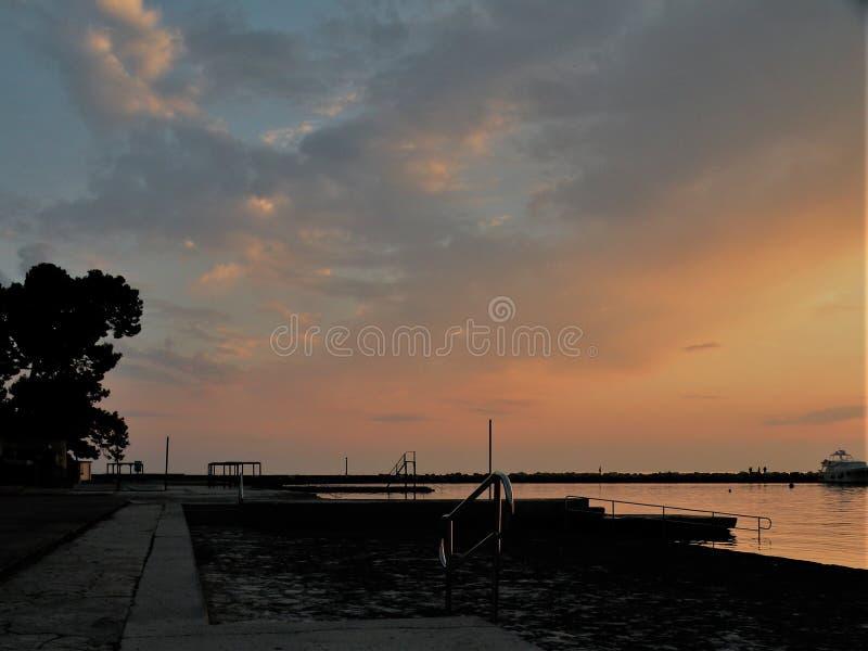 Faro all'estremità del pilastro delle pietre, tramonto sopra il mare adriatico, Croazia, Europa Mare arancio e calmo, siluetta, r fotografie stock libere da diritti