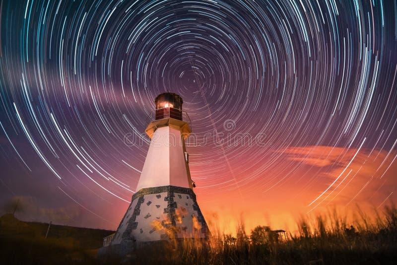Faro con el cielo nocturno en los rastros de las estrellas del fondo fotos de archivo libres de regalías