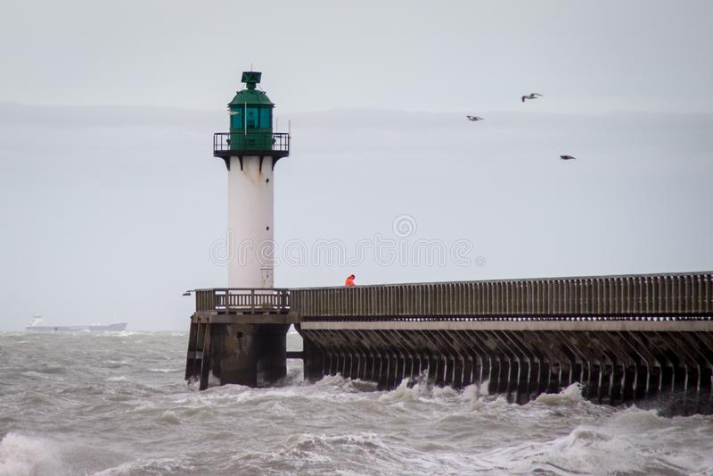 faro con il pilastro sul pomeriggio con il cielo nebbioso alla spiaggia del porto di Calais Franco Francia fotografia stock libera da diritti