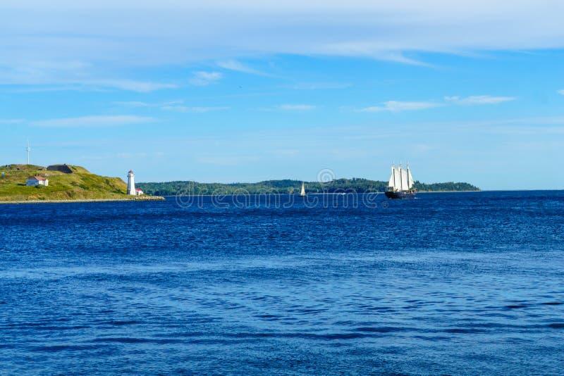Faro de Georges Island, y un velero, en Halifax fotos de archivo libres de regalías