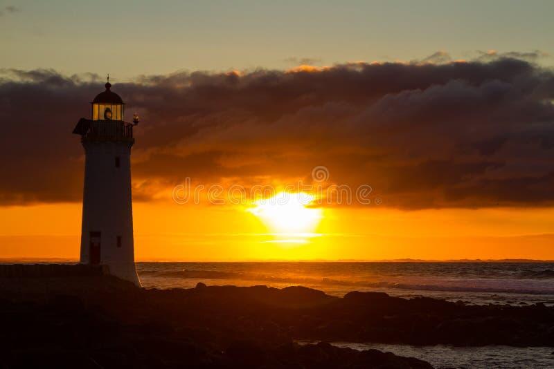Faro de hadas portuario, salida del sol roja que brilla intensamente de VIC fotografía de archivo