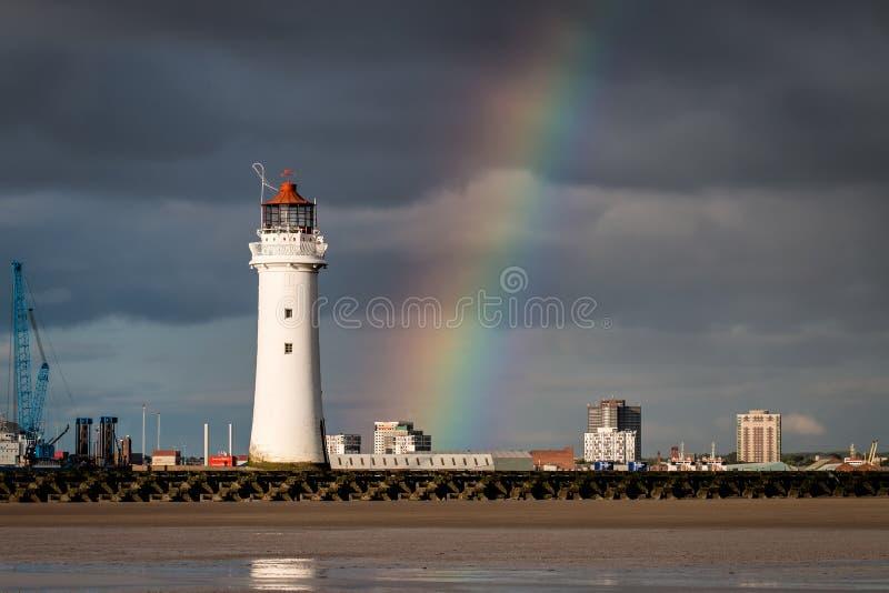 Faro de la roca de la perca con un arco iris fotos de archivo
