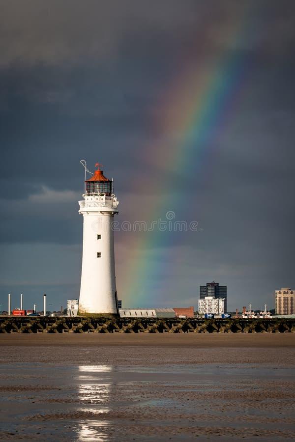 Faro de la roca de la perca con un arco iris imagenes de archivo