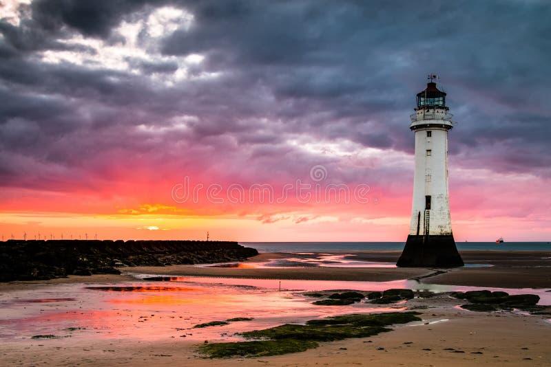 Faro de la roca de la perca en la puesta del sol fotos de archivo