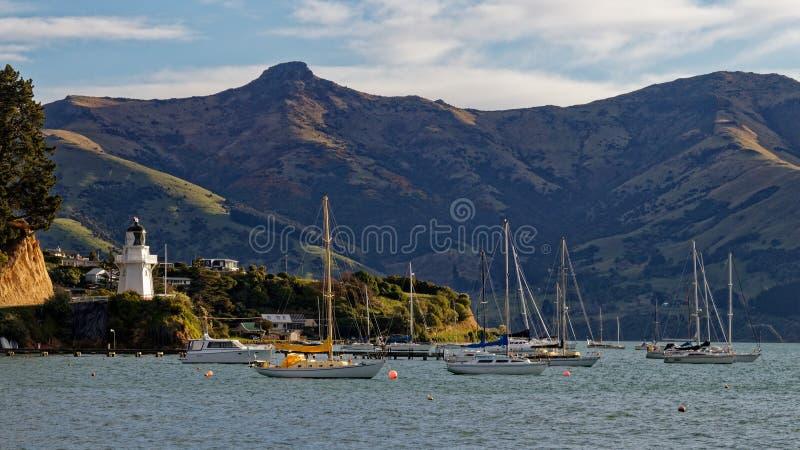 Faro di Akaroa e porto, penisola delle banche, Nuova Zelanda immagine stock