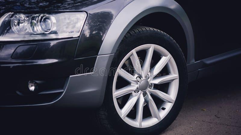 Faro di un'automobile nera moderna Le ruote anteriori dell'automobile Dettagli moderni di esterno dell'automobile fotografia stock