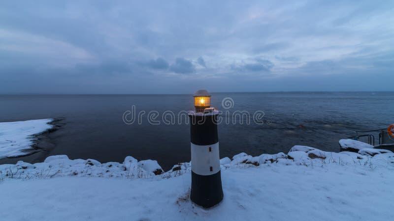 Faro en el lago en el invierno Finlandia fotografía de archivo libre de regalías