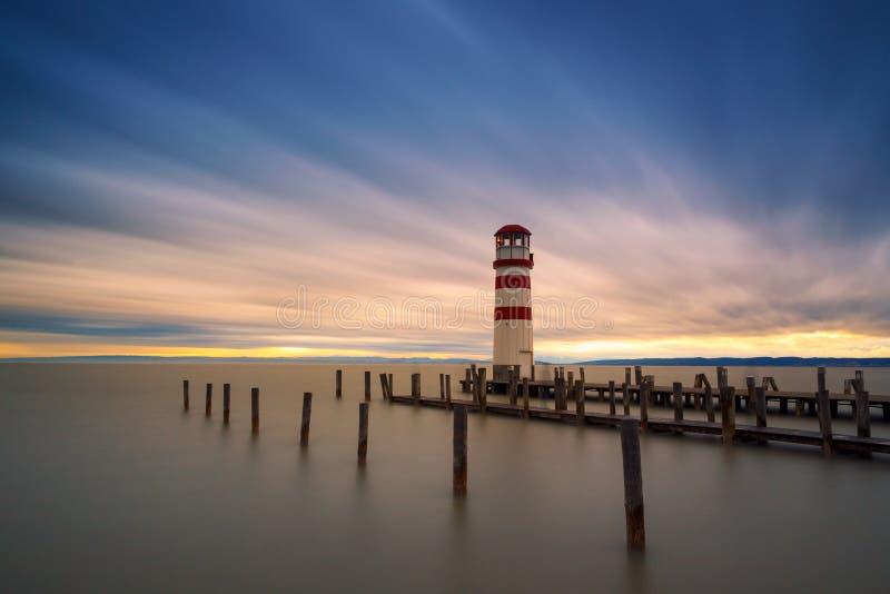Faro en el lago Neusiedl en la puesta del sol fotos de archivo