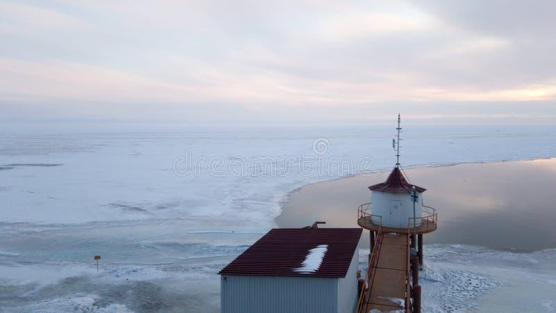 Faro en la fuente del río de Angara del lago Baikal Puesta del sol en Siberia escarchada en primavera foto de archivo