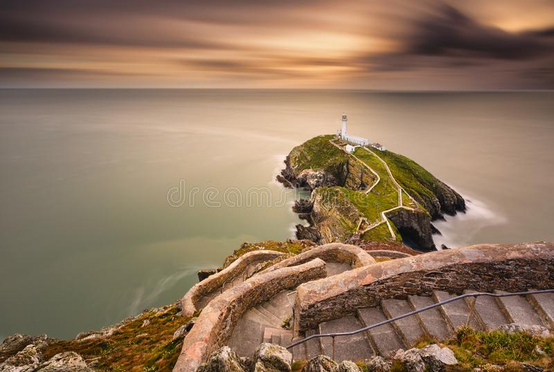 Faro en la isla costera con horizonte y hermosa puesta de sol imagenes de archivo