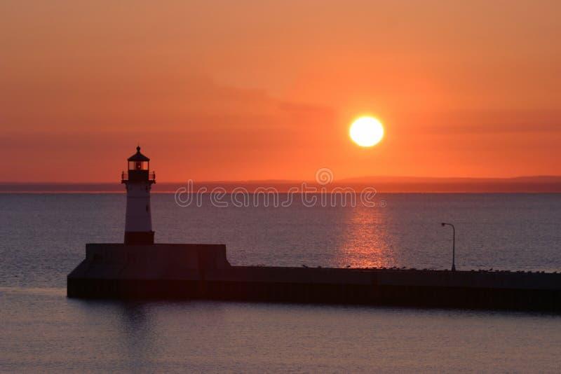 Faro en la puesta del sol imagenes de archivo