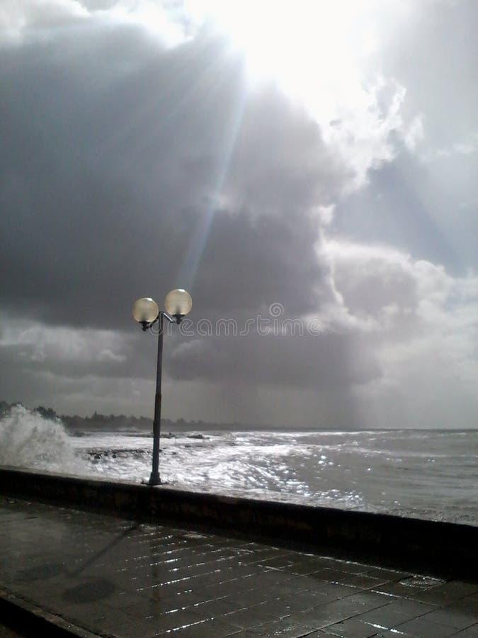 Faro en la tormenta Haz tempestuoso de las nubes de la tormenta del mar de la luz del sol entre las nubes foto de archivo