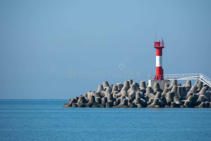 Faro en un rompeolas en el mar azul fotos de archivo libres de regalías