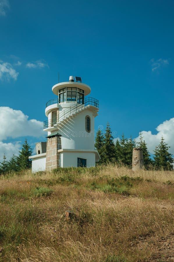 Faro encima de la colina cubierta por la hierba y los ?rboles imágenes de archivo libres de regalías