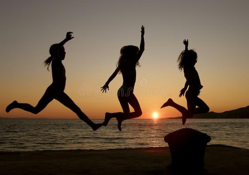 Faro, hermanas que saltan en puesta del sol imagen de archivo