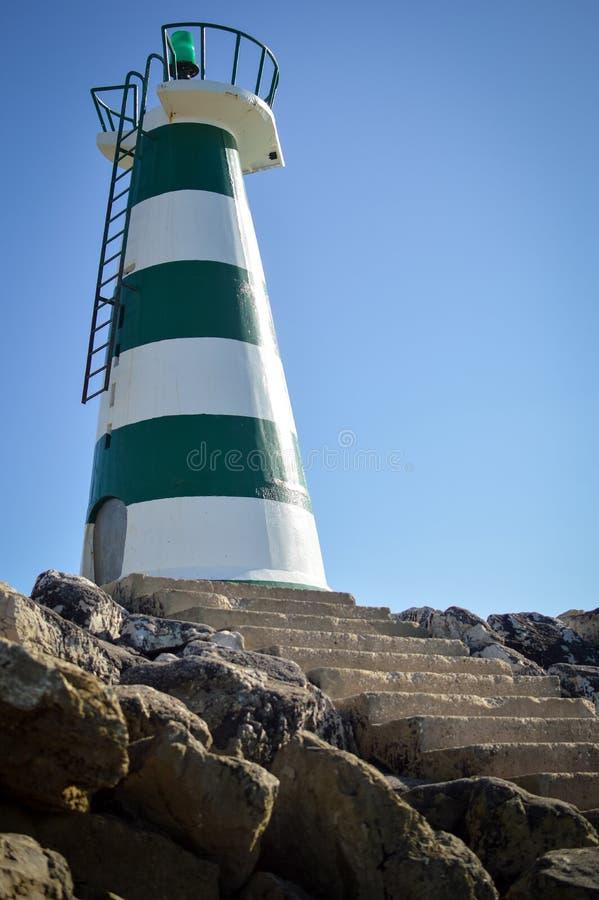 Faro hermoso con el sol brillante en el top en el cielo fotos de archivo
