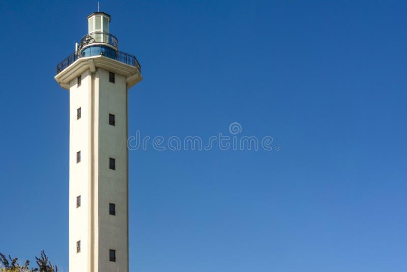 Faro a mezzogiorno un chiaro giorno sul fondo vuoto del cielo blu Carta da parati sul tema marino con un segnale fotografia stock libera da diritti