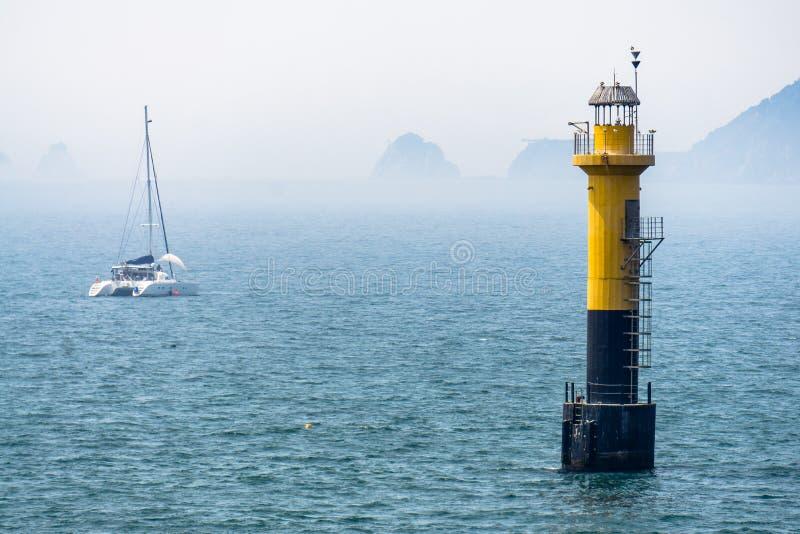Faro negro amarillo que se coloca en el mar Hay vario s imagenes de archivo