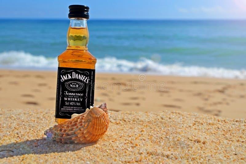 Faro, Portugal - 12/10/2018: el pequeño whisky de Jack Daniels de la botella en las cáscaras del océano se coloca en la arena Par fotos de archivo
