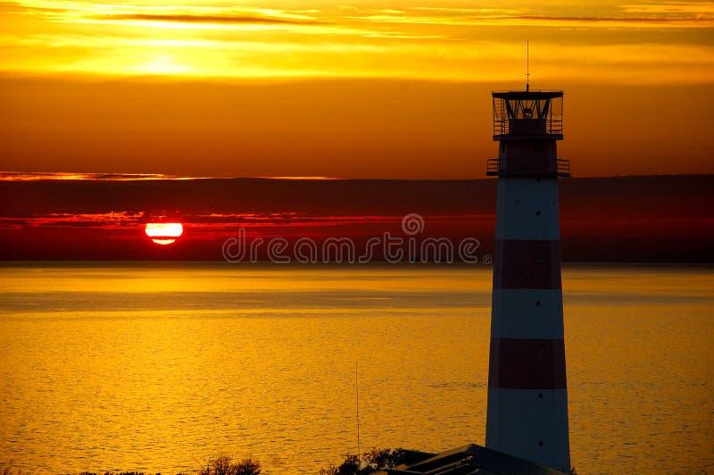 Faro rojo con el haz luminoso en la puesta del sol El top imagen de archivo