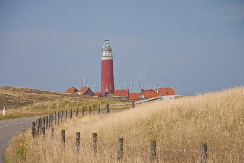 Faro rojo, pequeñas casas en Texel fotografía de archivo
