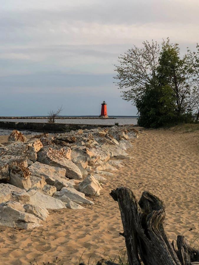 Faro rojo por la línea de la playa rocosa y la playa arenosa foto de archivo libre de regalías