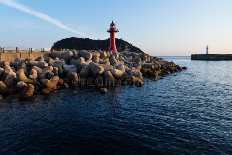 Faro rojo y blanco en un malecón con wavebreakers en Seogwipo, isla de Jeju, Corea del Sur fotografía de archivo libre de regalías